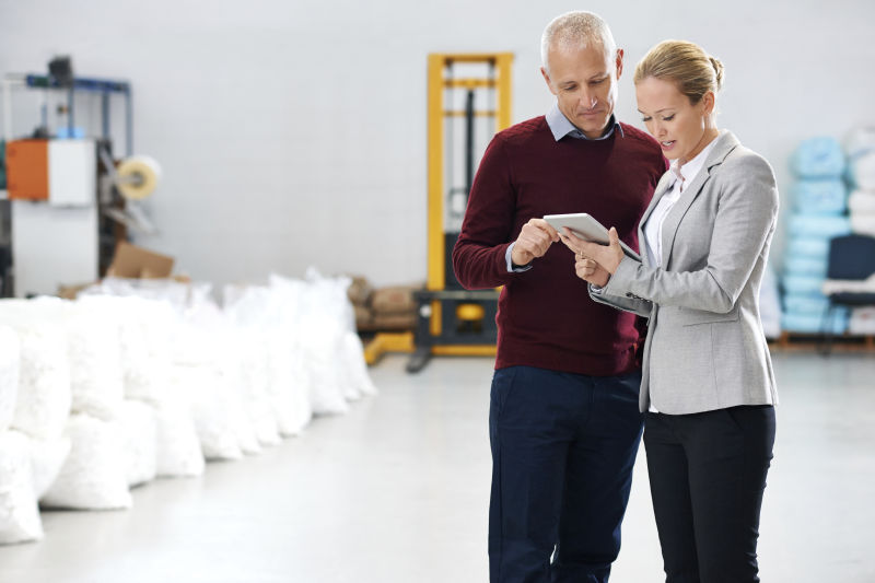 Shot of two factory managers using a tablet during a warehouse inspection