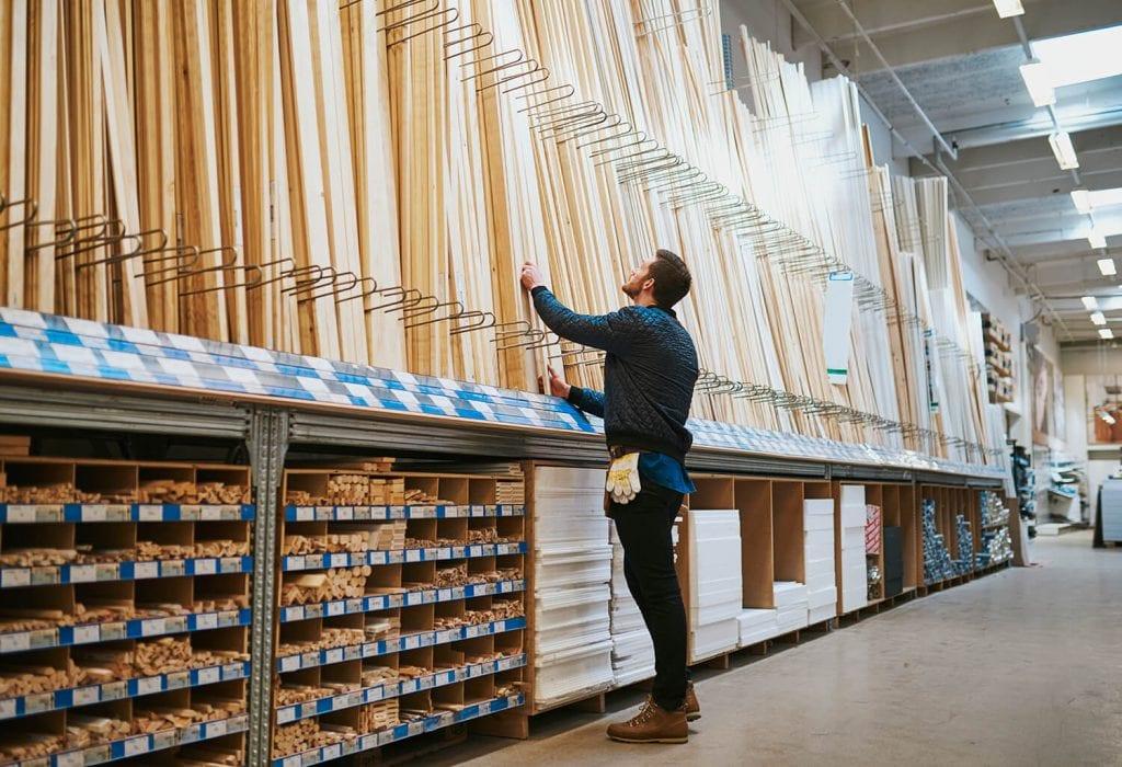 Man selecting timber from a shelf at timber merchants
