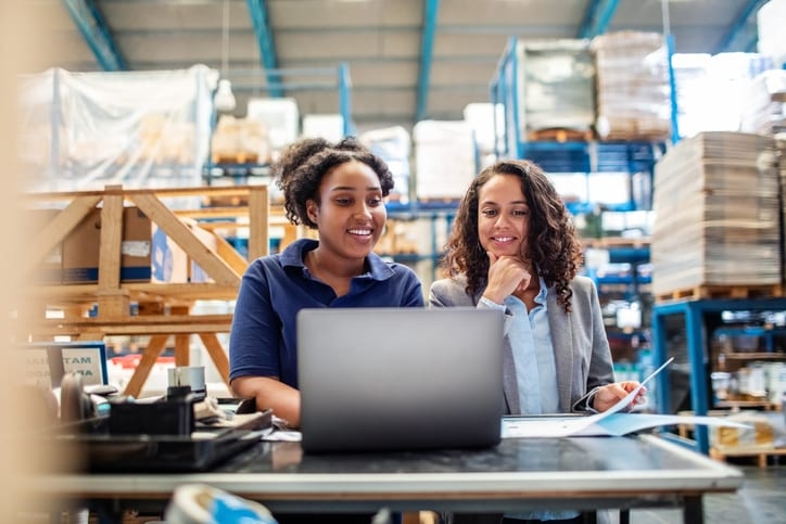 warehouse worker and manager smiling at laptop
