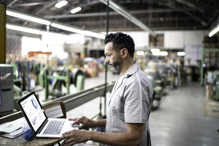 technician working on laptop in warehouse