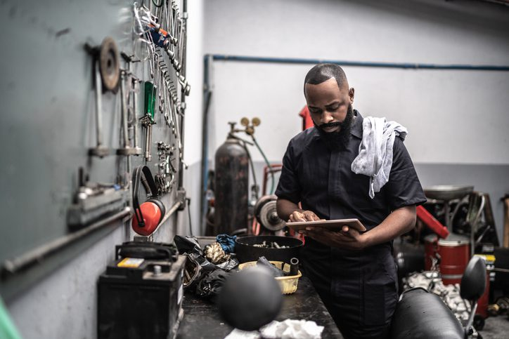 man in his workshop looking at his tablet